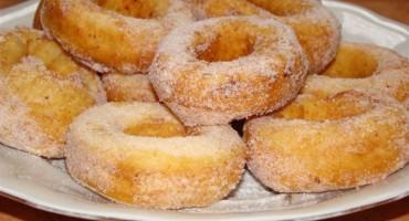 Oponki serowe posypane cukrem pudrem leżące na białym talerzu