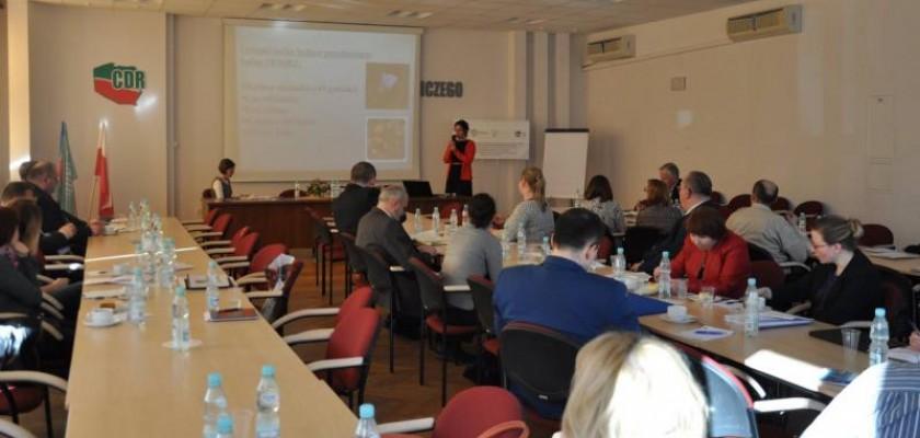 kobieta w czerwonym swetrze przemawia do ludzi podczas Spotkania informacyjno-szkoleniowego dla pracowników WODR