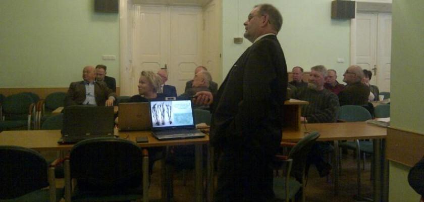 mężczyzna w czarnym garniturze i pilotem w ręku podczas prezentacji