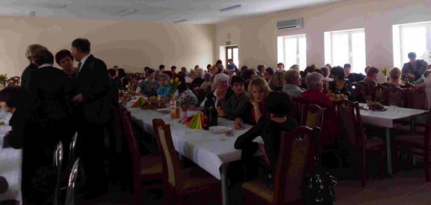 ludzie siedzący przy stołach w sali podczas dnia kobiet