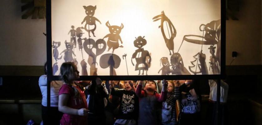 Zdjęcie przedstawia dzieci z kukiełkami postaci filmowych, pokazujących ich cienie na podświetlonympłótnie