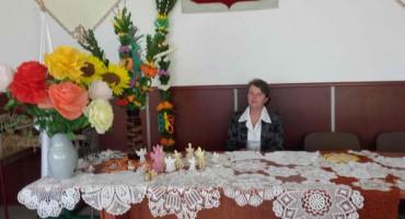Siedząca Pani Lucyna Jędrzejczyk przy palmach i kwiatach oraz serwetkach na stole
