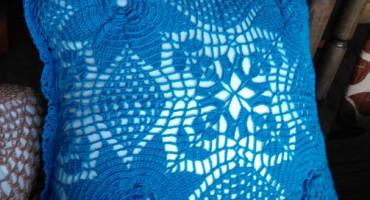 Zdjęcie prZdjęcie przedstawia niebieską poszewkę wykonaną na szydełkuzedstawia poszewkę wykonaną na szydełku