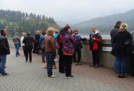grupa ludzi stojąca na placu wyłorzonym kostką w ogrodach kapias