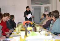 kobieta przemawiająca do grupy kobiet siedzących przy stole