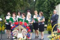 grupa kobiet na scenie w podobnych strojach oraz zielonymi teczkami w dłoniach