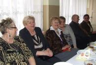 grupa kobiet oraz mężczyzna przy stole podczas obchodów dnia kobiet