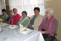 grupa starszych kobiet przy stole podczas obchodów dnia kobiet