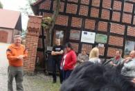 zbiórka ludzi obok budynku z czerwonej cegły i drzewa