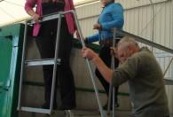 dwie kobiety stojące na metalowym podeście oraz mężczyzna wchodzący do nich po drabinie
