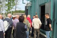 grupa ludzi wchodząca do zielonego budynku biogazowni