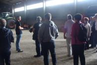 grupa ludzi zwiedzające stodołe, w tle zielony traktor