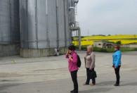 trójka kobiet stojąca pod dużymi srebrnymi silosami na terenie biogazowni