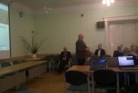 mężczyzna w brązowej marynarce przemawia do rolników w sali wykładowej