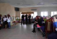 trzech mężczyzn w garniturach stoi na sali pełnej kobiet podczas obchodów dnia kobiet