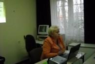 kobieta w pomarańczowej marynarce siedzi przy biurku