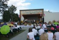 Zdjęcie przedstawia występ zespołu ludowego na scenie i podziwiającą ją publiczność