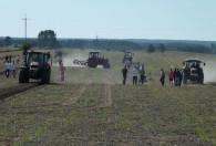 pięć traktorów oraz grupa ludzi na polu podczas pokazu